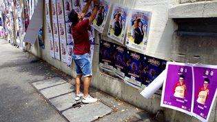 """Le comédien Franck Nouzies accroche les affiches de son spectacle, """"Les monologues de Feydeau"""", à Avignon, le 6 juillet 2021. (JEREMIE LAURENT-KAYSEN)"""