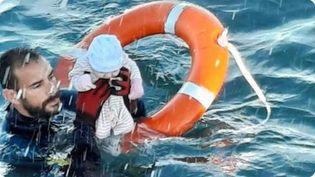 Capture d'écran de la photo postée par la Garde civile espagnole sur Twitter le 19 mai 2021, où l'on voit un sauveteur sortir des eaux un bébé à Ceuta. (GUARDIA CIVIL / TWITTER)