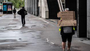 """A Paris, cet homme vêtu d'un gilet jaune était seul pour porter sa pancarte, sur laquelle était notamment écrit """"Nous avons droit aux miettes, nous voulons 100%"""". (MARTIN BUREAU / AFP)"""