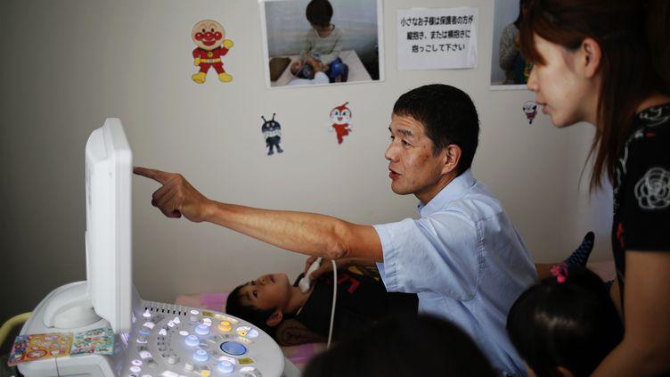 Un médecin procède, le 13 septembre 2013,à l'examen de la thyroïded'un enfant à Iwaki. Cette ville, située à une soixantaine de kilomètres de la centrale nucléaire de Fukushima,a servi de refuge à des milliers de sinistrés des zones évacuées. (DAMIR SAGOLJ / REUTERS)