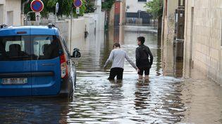 Des habitants deChateaubriant (Loire-Atlantique) marchent dans une rue inondée après les fortes pluies d'orages, le 12 juin 2018. (RONAN HOUSSIN / CROWDSPARK)