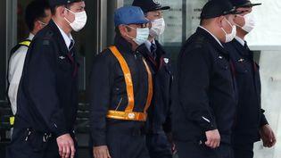 Carlos Ghosn (avec une casquette bleue), le 6 mars 2019, à la sortie d'un centre de détention de Tokyo. (BEHROUZ MEHRI / AFP)