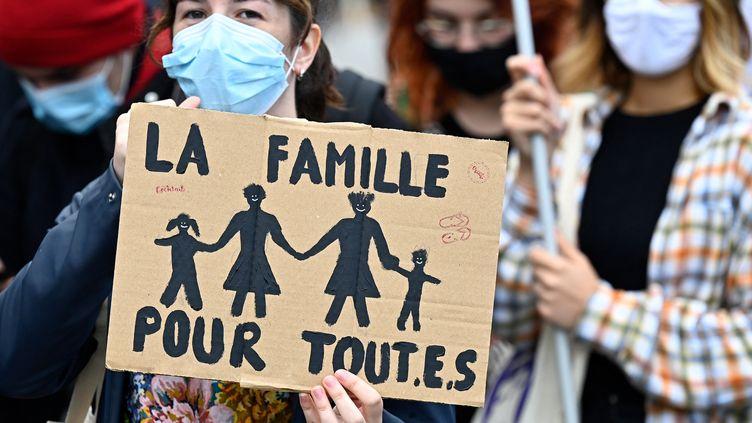 """Une manifestante masquée tient une pancarte """"Une famille pour tout.e.s"""" lors d'une manifestation en faveur du projet de loi de bioéthique sur la Procréation Médicalement Assistée (PMA), à Rennes (Bretagne), le 10 octobre 2020. (DAMIEN MEYER / AFP)"""
