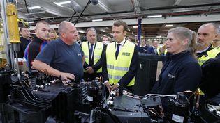 Emmanuel Macron avec des employés de Whirpool, lors de sa visite dans l'usine à Amiens, le 3 octobre 2017. (PHILIPPE WOJAZER / POOL)