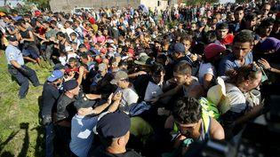Un cordon de policiers croates tente de contenir les migrants qui attendent de monter dans des bus à Tovarnik (Croatie), près de la frontière avec la Serbie, le 17 septembre 2015. (ANTONIO BRONIC / REUTERS)