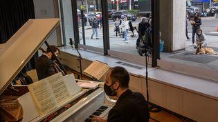 Les musiciens Michael Katz et Spencer Myer se produisent dans le cadre de concerts derrière une vitrine organisés par the Kaufman Music Center's, le 25 mars 2021 à New York (ANGELA WEISS / AFP)