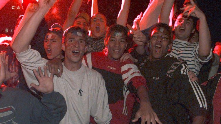 Des jeunes français expriment leur joie après la victoire de la France faceà la Croatie en demi-finale de Coupe du monde, le8 juillet 1998. (JACK GUEZ / AFP)