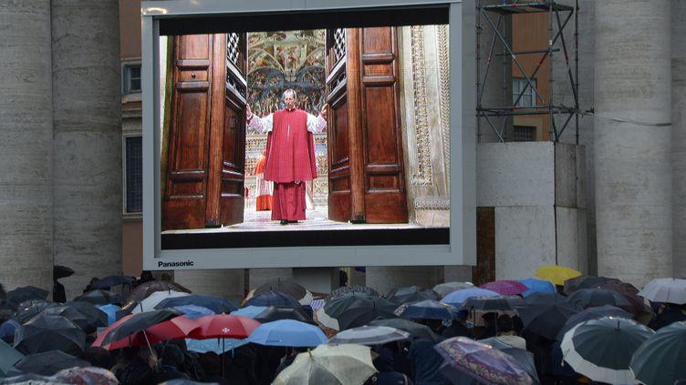 Sur la place Saint-Pierre,où un écran géant a été installé pour suivre l'entrée des cardinaux dans la chapelle Sixtine, le12 mars 2013. (ANDREAS SOLARO / AFP)