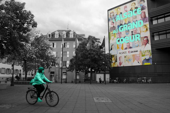 Une cycliste passe devant une affiche déployée sur le siège du conseil départemental du Bas-Rhin, à Strasbourg, le 8 octobre 2020. (YANN THOMPSON - PIERRE-ALBERT JOSSERAND / FRANCEINFO)
