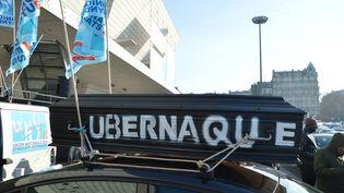 """Un cercueil portant l'inscription """"Ubernaque"""" est fixé sur un VTC, pendant le blocage de la porte Maillot, à Paris, le 15 décembre 2016. (ALPHA CIT / CITIZENSIDE / AFP)"""