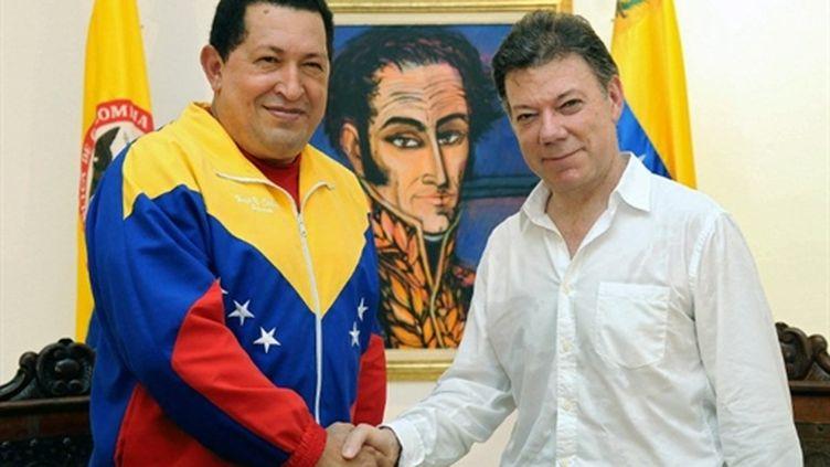 Hugo Chavez (à gauche) et Juan Manuel Santos (à droite) se serrant la main sous le portrait de Bolivar le 10 août 2010 (AFP - Felipe Pinzon)