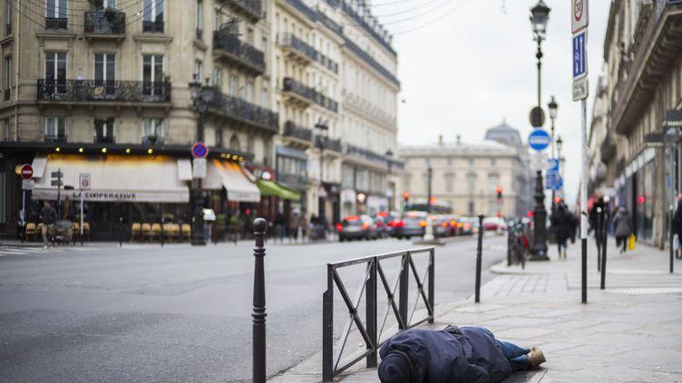 Un sans-abri dort sur le trottoir à Paris, le 16 janvier 2017. (MARTIN BUREAU / AFP)