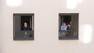 Des habitants de Vienne (Autriche) regardent, depuis leur fenêtre, un concert donné par des chanteursaccompagnés par unorchestre, lors du confinement, le 30 mai 2020. (JOE KLAMAR / AFP)