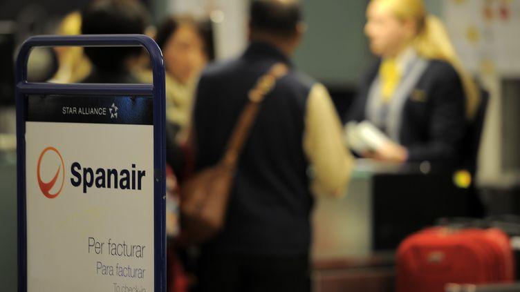 Des passagers au comptoir d'enregistrement de la compagnie Spanair à l'aéroport de Barcelone (Espagne), le 27 janvier 2012. (LLUIS GENE / AFP)