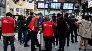 Des salariés de la SNCF aident des usagers à la gare Saint-Lazare, à Paris, le 1er juin 2016, lors d'une grève. (ANADOLU AGENCY / AFP)