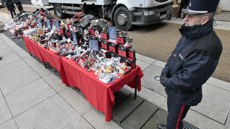 Un gendarme devant des articles de contrefaçon avant leur destruction, à Paris, le 27 janvier 2011. (JACQUES DEMARTHON / AFP)