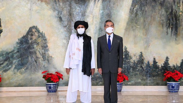 Le conseiller d'Etat chinois et ministre des Affaires étrangères Wang Yi rencontre le mollah Abdul Ghani Baradar, chef politique des talibans, à Tianjin (nord de la Chine), le 28 juillet 2021. (LI RAN / XINHUA / AFP)