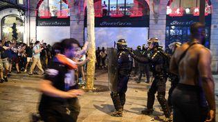 Des CRS interviennent sur les Champs-Elysées, à Paris, le 15 juillet 2018. (ERIC FEFERBERG / AFP)