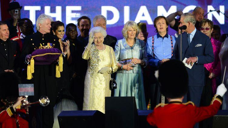 La reine Elizabeth II salue la foule sur scène après un concert pop géant à Londres (Grande-Bretagne) à l'occasion de son jubilé de diamant, le 4 juin 2012. (LEON NEAL / AFP)