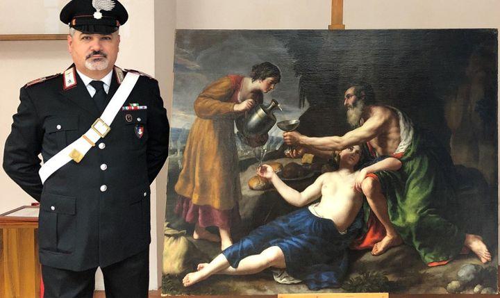 """Un carabinier italien posté à côté du tableau de Poussin """"Loth avec ses deux filles lui servant à boire"""" (photo publiée le 1er avril 2021) (HANDOUT / CARABINIERI PRESS OFFICE / AFP)"""