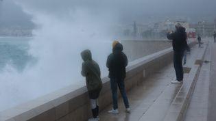 Des personnes observent les vagues à Nice (Alpes-Maritimes), le 2 octobre 2020, lors du passage de la tempête Alex. (MAXPPP)
