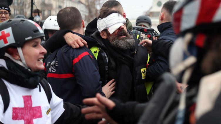 Jérôme Rodrigues est évacué après avoir été blessé à l'œil par un projectile, place de la Bastille, le 26 janvier 2019. (ZAKARIA ABDELKAFI / AFP)