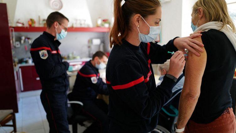Une patiente reçoit une dose du vaccin contre le Covid-19 par une femme sapeur-pompier à son domicile, dans l'Hérault, le 19 mars 2021. (SYLVAIN THOMAS / AFP)