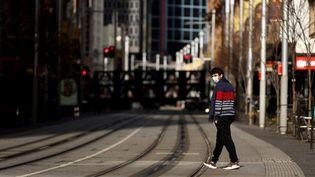 Un homme marche dans les rues désertes de Sydney (Australie), le 13 juillet 2021. (BRENDON THORNE / AFP)