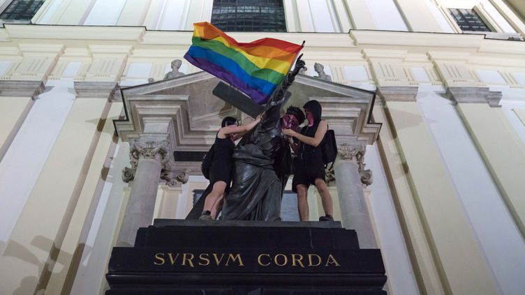 Des militants placent un drapeau arc-en-ciel et un bandana aux symboles anarchistes sur une statue du Christ de l'église de la Sainte-Croix, le 29 juillet 2020 à Varsovie (Pologne). (SOCIAL MEDIA / X04130)