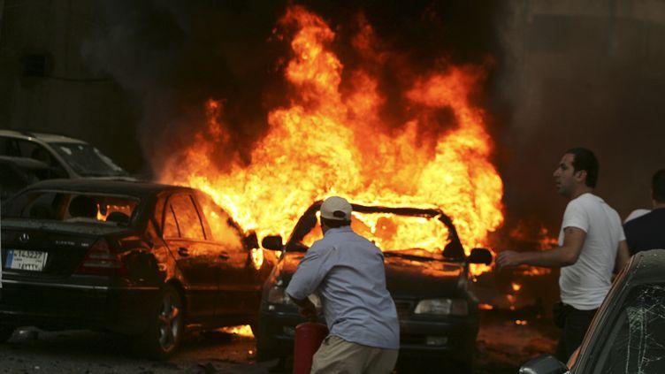 Un homme tente d'éteindre l'incendie après un attentat à la voiture piégée, le 9 juillet 2013 à Beyrouth (Liban). (REUTERS)