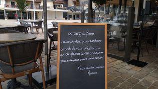 Un panneau indique que le pass sanitaire est obligatoire pour manger à la brasserie Honorine de Deauville (Calvados), dimanche 25 juillet. (CELINE AUTAIN / RADIO FRANCE)