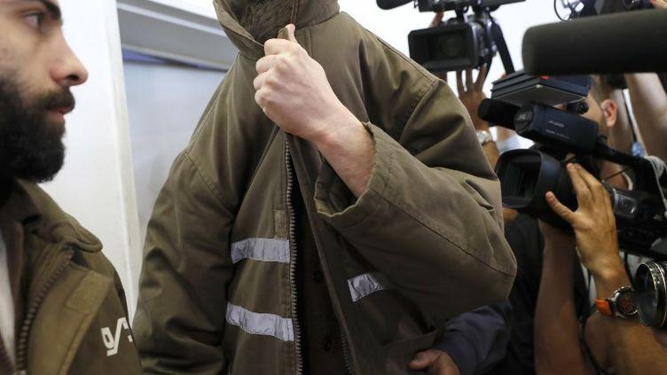 Le Français Romain Franck,le visage camouflé sous sa veste de prisonnier, au tribunal deBeer-Sheva (Israël), le 19 mars 2018. (JACK GUEZ / AFP)