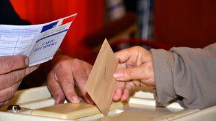 Un électeur met son bulletin dans l'urne à Marseille, le 22 mars 2015, lors du premier tour des départementales. (GERARD BOTTINO / CITIZENSIDE / AFP)