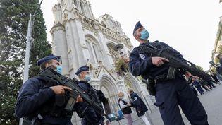 Les forces de l'ordre devant la basilique Notre-Dame à Nice où trois personnes ont été tuées dans un attentat, jeudi 29 octobre 2020. (ERIC GAILLARD / AFP)