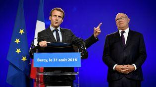 Emmanuel Macron (gauche) et Michel Sapin lors de la passation de pouvoirs, au ministère de l'Economie, à Paris, le 31 août 2016. (PHILIPPE LOPEZ / AFP)