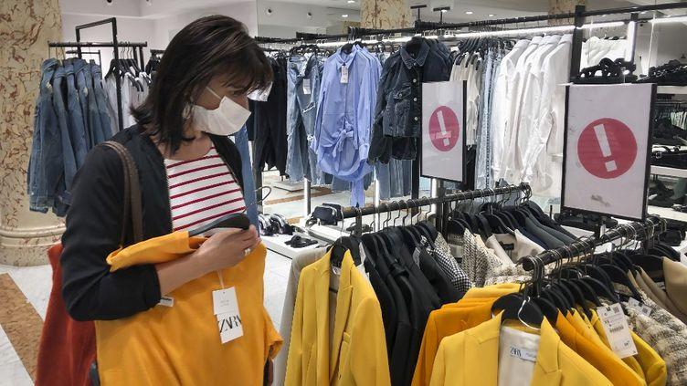 Une femme porte un masque de protection dans un magasin de prêt-à-porter, à Nice (Alpes-Maritimes), le 19 mai 2020. (ARIE BOTBOL / HANS LUCAS / AFP)