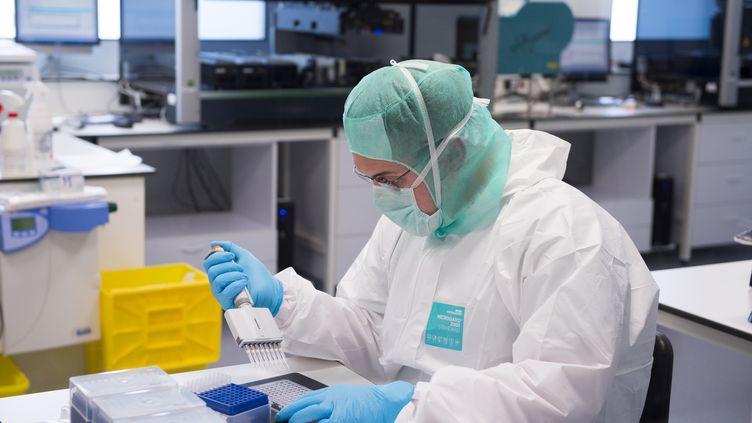 Un expert scientifique en médecine légale collecte des empreintes ADN à l'l'Institut de recherches criminelles de la gendarmerie nationale, installé à Pontoise, le 19 mai 2015. (MARTIN BUREAU / AFP)