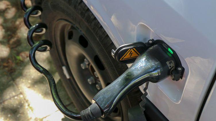 Une voiture électrique en cours de recharge, àAix-la-Chapelle, en Allemagne. (YANN SCHREIBER / AFP)
