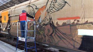 "Un graffeur repeint le train ""Rungis"" à la gare d'Austerlitz à Paris, samedi 22 octobre 2016. (WILFRIED DEMARET)"