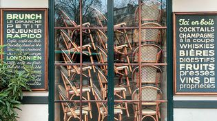 Des chaises et des tables sont empilées derrière la vitrine d'un café fermé à Paris, le 15 janvier 2021. (JEROME LEBLOIS / HANS LUCAS / AFP)