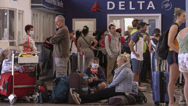 Des touristes patientent à l'aéroport de La Havane (Cuba), le 24 mars 2020. (ADALBERTO ROQUE / AFP)