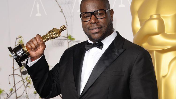 """Le réalisateur britannique Steve McQueen brandit l'Oscar du meilleur film obtenu pourson film """"Twelve Years a Slave"""", le 2 mars 2014 à Hollywood (Etats-Unis). (JASON MERRITT / GETTY IMAGES NORTH AMERICA / AFP)"""