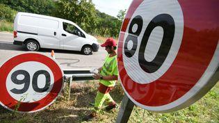 Des employés de laDirection interdépartementale des routes de l'Est remplacent des panneaux de limitation de vitesse.Modifier le media (2856183)  (SEBASTIEN BOZON / AFP)