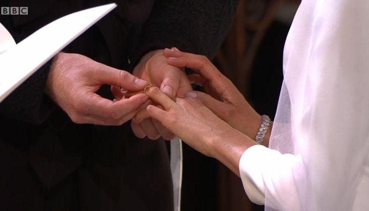 Harry remet la bague de mariée à l'annulaire de Meghan. On aperçoit le bracelet Cartier.  (Capture écran BBC)