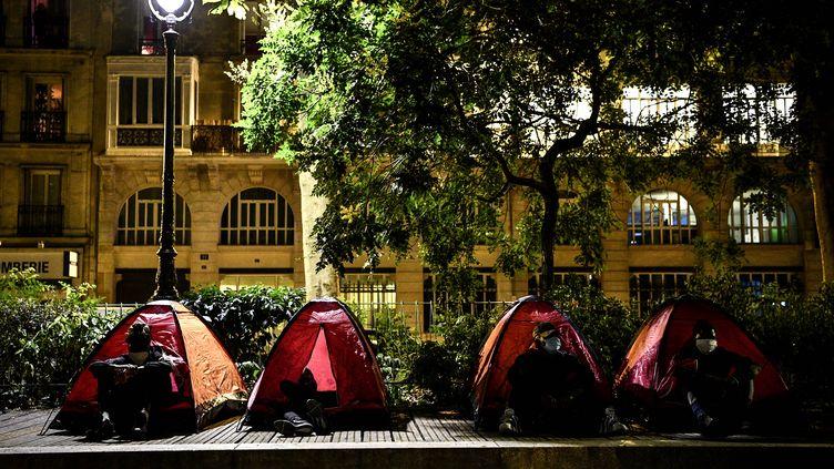 Des migrants sont assis dans des tentes installées par Médecin sans frontière (MSF) et Utopia 56, dans un parc parisien, le 29 juin 2020. (CHRISTOPHE ARCHAMBAULT / AFP)