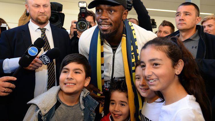 Usain Bolt pose avec des enfants à son arrivée en Australie, le 18 août 2018. (SAEED KHAN / AFP)