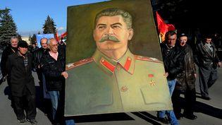Un portrait de Joseph Staline, porté dans une rue de Gori (Géorgie), la ville natale du dictateur, le 21 décembre 2014, à l'occasion du 135e anniversaire de sa naissance. (VANO SHLAMOV / AFP)
