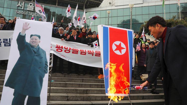Des manifestants sud-coréens brûlent un drapeau nord-coréen à côté d'une photo de Kim Jong-Un lors d'un rassemblement anti-nord-coréen à Séoul le 22 janvier 2018. (- / YONHAP)