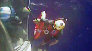 """Capture d'écran d'une vidéo filmée le 4 octobre 2015, montrant un garde-côte hélitreuillé après avoir récupéré une bouée de sauvetage du cargo """"El Faro"""", au large des Etats-Unis. (US COAST GUARD / AFP)"""