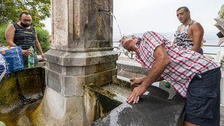 Des hommes se rafraîchissent à une fontaine, mercredi 11 août 2021 à Messine (Italie). (GIOVANNI ISOLINO / AFP)